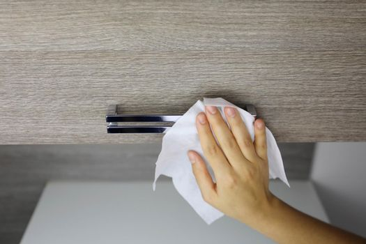 COVID-19 Pandemic Coronavirus Woman Hand Disinfect Handle Furniture Kitchen with Wet Wipes Alcohol Cleaning Against Coronavirus Disease 2019 Outbreak Contamination Prevention