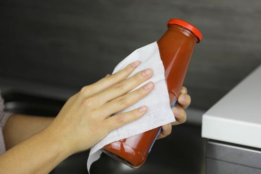 COVID-19 Pandemic Coronavirus Woman Disinfect Bottle of Tomato Puree with Wet Wipes Cleaning Against Coronavirus Disease 2019 Outbreak Contamination Prevention