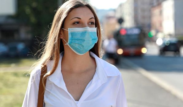 COVID-19 Pandemic Coronavirus Woman in city street wearing surgical mask protective for spreading of disease virus SARS-CoV-2. Girl with protective mask on face against Coronavirus Disease 2019.