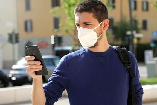 COVID-19 Pandemic Coronavirus Young Man Wearing KN95 FFP2 Mask Using Smart Phone App in City Street to Aid Contact Tracing and Self Diagnostic in Response to the Coronavirus Pandemic 2019