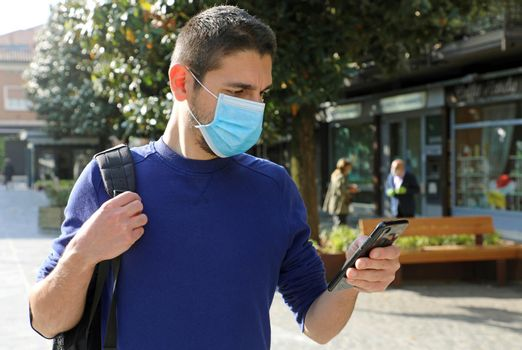 COVID-19 Pandemic Coronavirus Young Man Wearing Surgical Mask Using Smart Phone App in City Street to Aid Contact Tracing and Self Diagnostic in Response to the Coronavirus Pandemic 2019