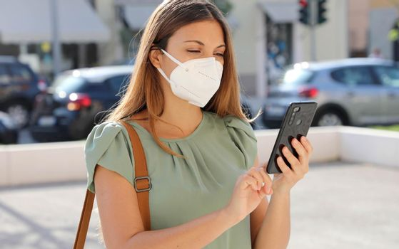 COVID-19 Mobile Application Young Woman Wearing KN95 FFP2 Mask Using Smart Phone App in City Street to Aid Contact Tracing and Self Diagnostic in Response to Coronavirus Disease 2019