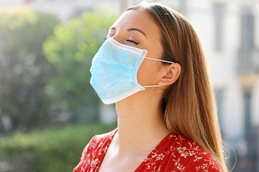 COVID-19 Pandemic Coronavirus Close up of young woman with surgical mask breathing outdoor