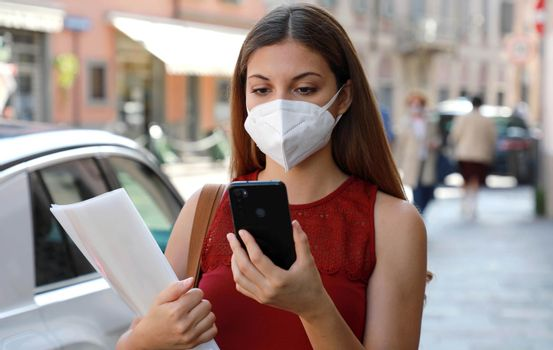 COVID-19 Global Economic Crisis Unemployed Woman with Mask Looking for Work with Job Recruiting App on Mobile Phone in City Street Delivering Curriculum Vitae