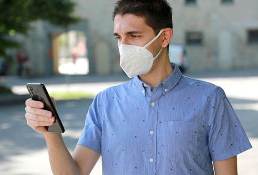 COVID-19 Mobile Application Young Man Wearing KN95 FFP2 Mask Using Smart Phone App in City Street to Aid Contact Tracing and Self Diagnostic in Response to the Coronavirus Pandemic 2019