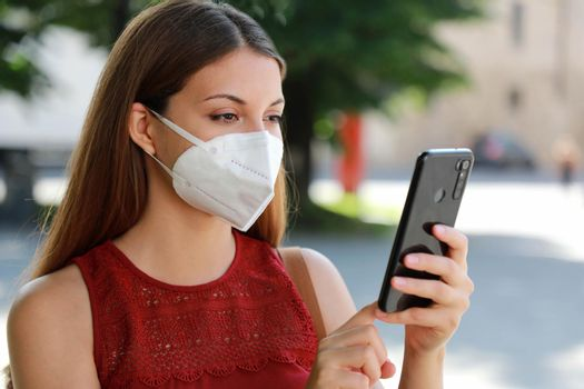 COVID-19 Close Up Young Woman Wearing KN95 FFP2 Mask Using Smart Phone App in City Street to Aid Contact Tracing and Self Diagnostic in Response to Coronavirus Disease 2019