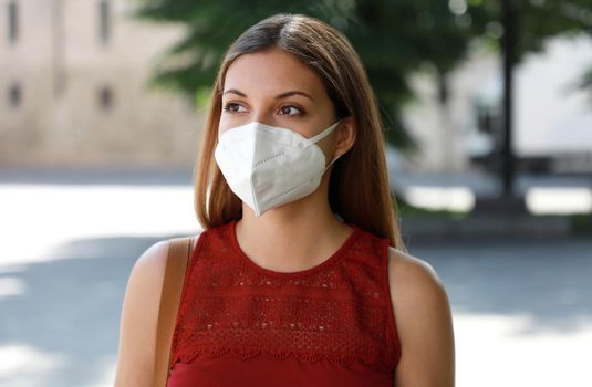 COVID-19 Worried girl in city street wearing KN95 FFP2 mask protective for spreading of disease virus SARS-CoV-2. Girl with protective mask on face against Coronavirus Disease 2019.