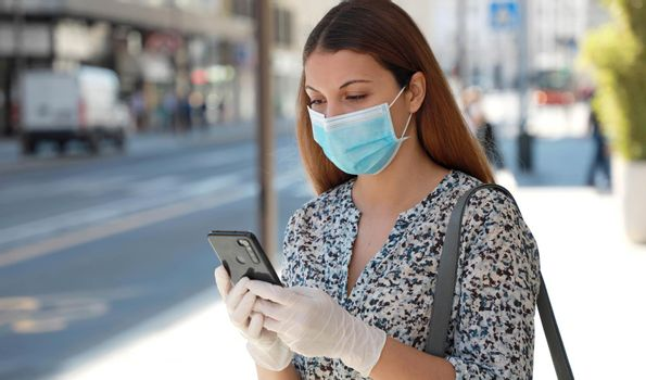 COVID-19 Woman Wearing Surgical Mask and Protective Gloves Using Mobile Phone Application in City Street to Aid Contact Tracing and Self Diagnostic in Response to SARS-CoV-2