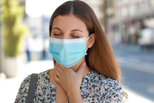 COVID-19 Close up Woman wearing surgical mask with sore throat outdoor. Portrait of woman with face mask against SARS-CoV-2 suffering throat pain in city street.