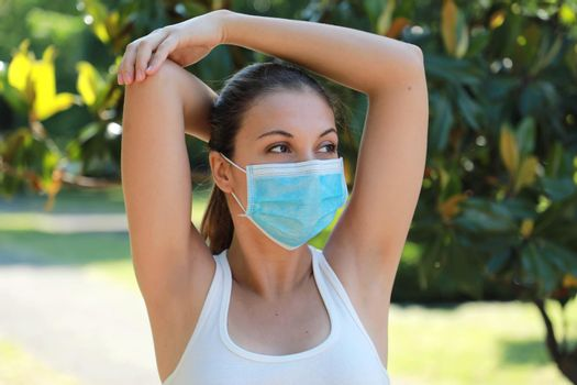 Armpit epilation hair removal sporty woman showing armpits outdoor. Girl stretching in park showing shaved armpits hairless. Happy relaxed woman with surgical mask laser hair removal concept.