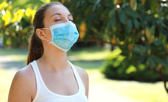 COVID-19 Close up of young sporty woman with surgical mask breathing in the park