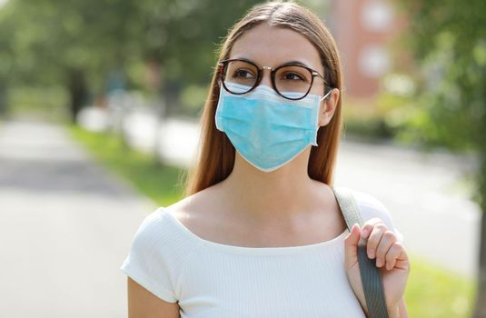 Young woman in city street wearing protective mask for spreading of disease virus SARS-CoV-2. Girl with surgical mask on face against Coronavirus Disease 2019.