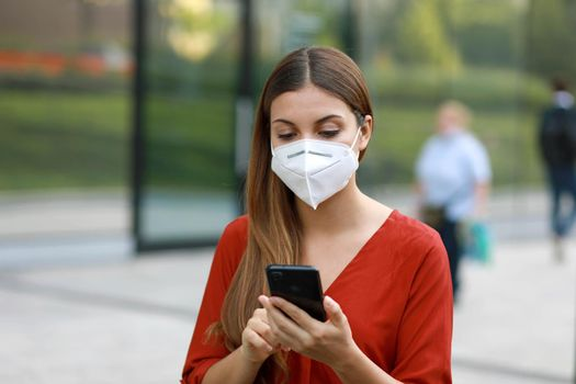 Young Woman Wearing KN95 FFP2 Mask Using Mobile Phone App in City Street to Aid Contact Tracing and Self Diagnostic in Response to Coronavirus Disease 2019