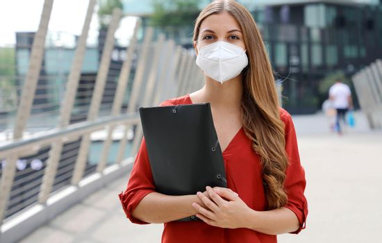 Unemployed serious woman with KN95 FFP2 protective mask looking worried at camera