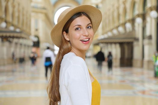 Close up of smiling fashion tourist woman visiting Vittorio Emanuele Gallery in the city of Milan, Italy