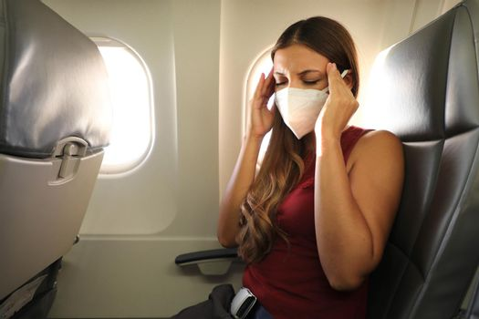 COVID-19 Young woman with KN95 FFP2 mask feeling unwell on plane. Fear of flying woman in airplane. Stress, headache, motion sickness and airsickness on plane during pandemic.