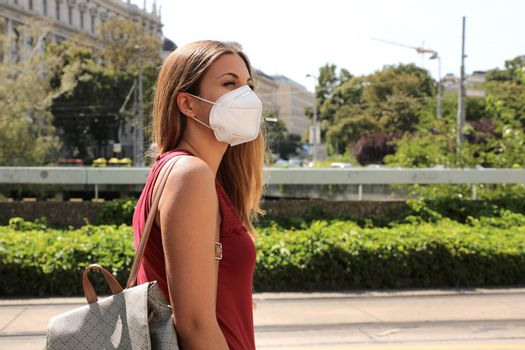 COVID-19 Woman in city street wearing KN95 FFP2 mask protective for spreading of disease virus SARS-CoV-2. Girl with protective mask on face against Coronavirus Disease 2019.