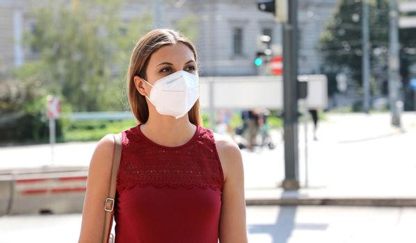 COVID-19 Woman walking in city street wearing KN95 FFP2 mask protective for spreading of disease virus SARS-CoV-2. Girl with protective mask on face against Coronavirus Disease 2019.