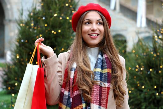 Portrait of young beautiful woman doing shopping on Christmas Eve