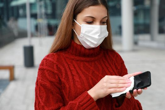 Portrait of woman with protective mask disinfecting cleaning mobile phone touch screen prevention wiping against contamination