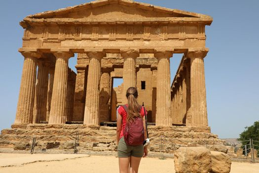Young woman looks at Concordia Temple in the Valley of the Temples Agrigento, Sicily. Traveler girl visits Greek Temples in Southern Italy.