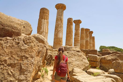 Young woman walking in the Valley of the Temples Agrigento, Sicily. Traveler girl visits Greek Temples in Southern Italy.