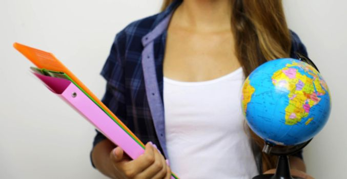 Blurred image of young woman student or teacher with folders and globe in her hands. Blurred banner background.
