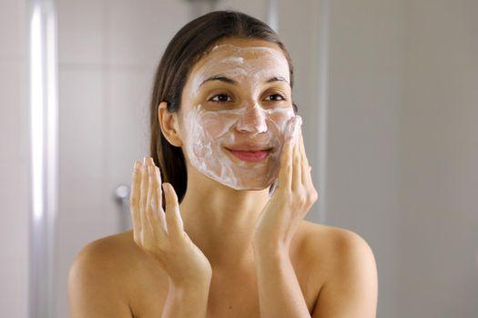 Skincare woman washing face  foaming soap scrubbing skin. Face wash exfoliation scrub soap woman washing scrubbing with skincare cleansing product. Enjoying relaxing time.