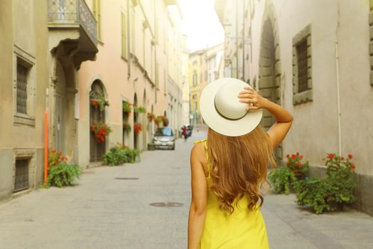 Back view of tourist woman walking and holding hat at Via Pignolo street in Bergamo old town, Italy.