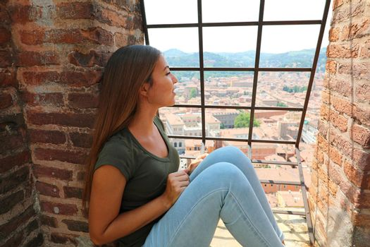 Europe travel woman looking at Bologna cityscape from the top of Asinelli tower, famous medieval tourist attraction in Italy