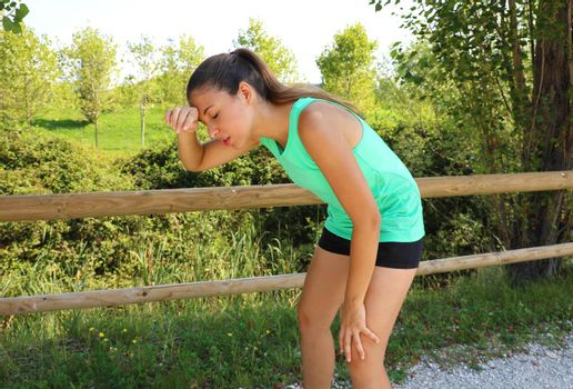 Woman bent over in exhaustion and catching her breath after a running session.
