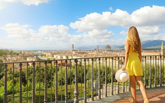 Beautiful woman in Florence birthplace of the Renaissance. Full length view of pretty girl enjoying panoramic view of Florence city in Tuscany, Italy.