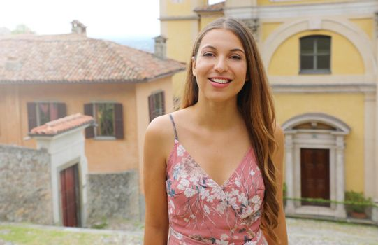 Young woman in Italian old town looks at camera.