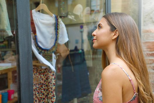 Elegant young fashion woman looking at showcase of clothing store.