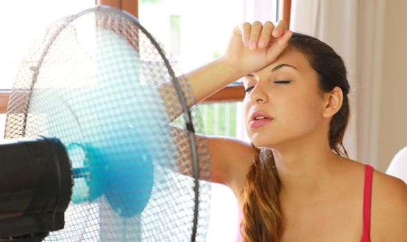 Unhappy student girl at home in hot summer day in front of working fan suffering from summer heat.