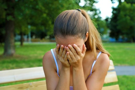 Bullying, discrimination or stress concept. Sad teenager crying alone in the park. Upset young female student having anxiety.
