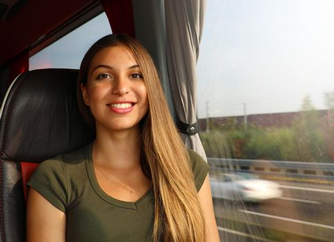 Smiling beautiful traveler woman on bus looking at camera. Concept public transportation commuter.