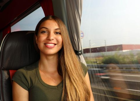 Happy cheerful beautiful traveler woman on bus looking at camera. Concept public transportation commuter.