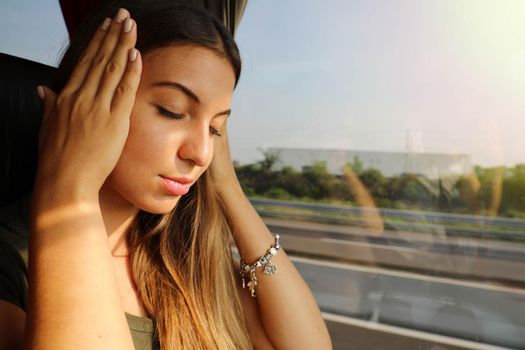 Young woman suffer sickness during travel on bus. Motion sickness tourist woman on bus with headache or nausea.