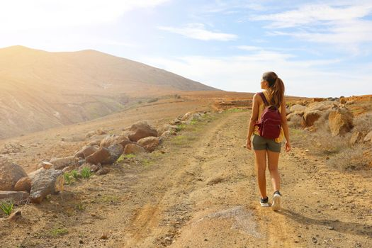 Hiker backpacker woman walking on pathway watching sunset