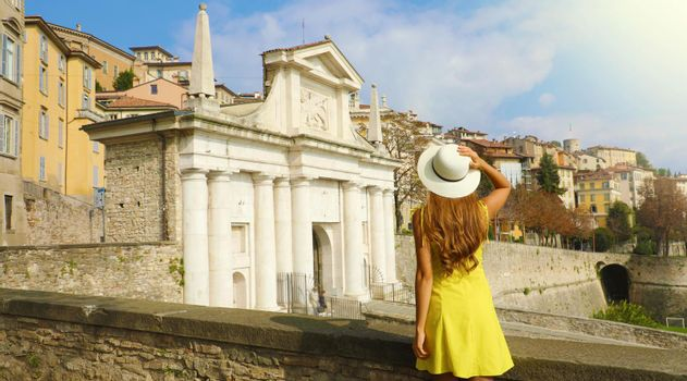 Beautiful young woman with hat enjoying view from walls of Porta San Giacomo gate and the Upper City of Bergamo, Italy.