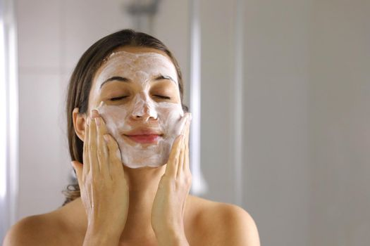 Skincare woman washing face  foaming facewash soap scrub on skin. Face wash exfoliation scrub soap woman washing scrubbing with skincare cleansing product. Enjoying relaxing time.