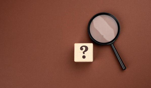 black magnifier on a brown background and question marks. The concept of uncertainty and the search for solutions