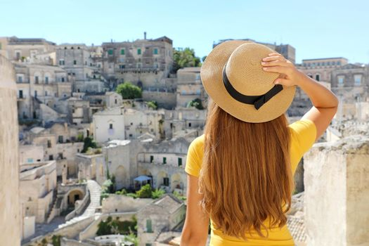 Young beautiful tourist woman visiting the historical town of Matera in Italy