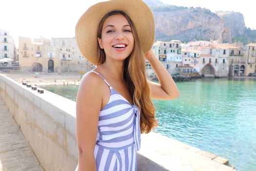 Laughing girl in a straw hat looking in the camera in Cefalu, Sicily