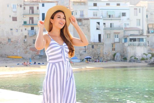 Beautiful young woman in overalls outfit enjoy the beach in summer resort in Italy