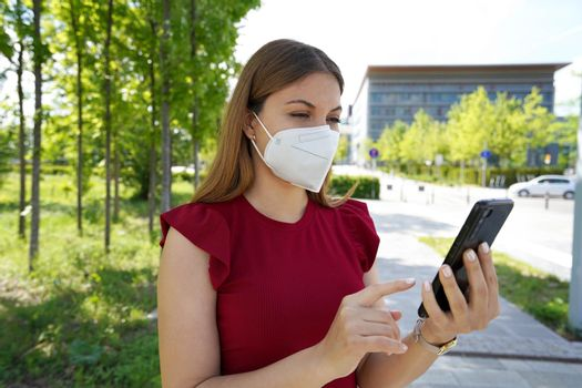 Young woman in city wears protective face mask KN95 FFP2 checks her smartphone