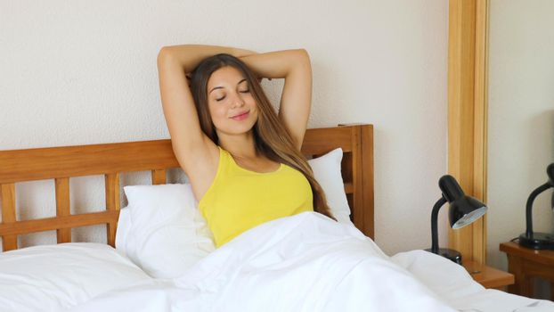 Girl stretching in bed after wake up