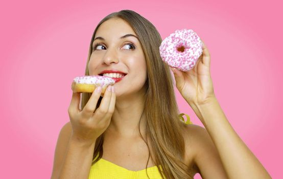 Close up portrait of a satisfied pretty girl eating donuts isolated over pink background.
