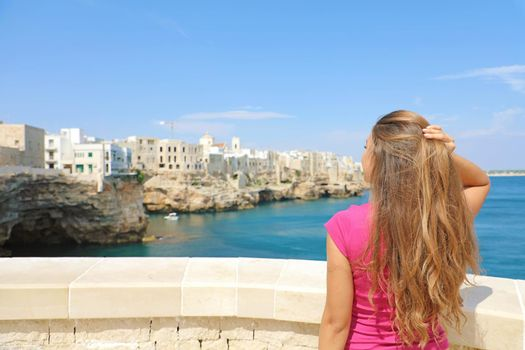 Summer holidays in Apulia. Back view of beautiful young woman enjoying Polignano a mare view, Mediterranean Sea, Italy.